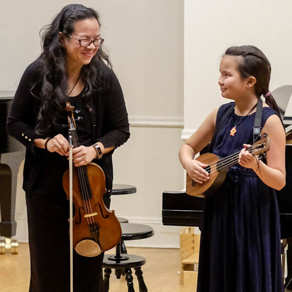 Mother and daughter performing at family concert